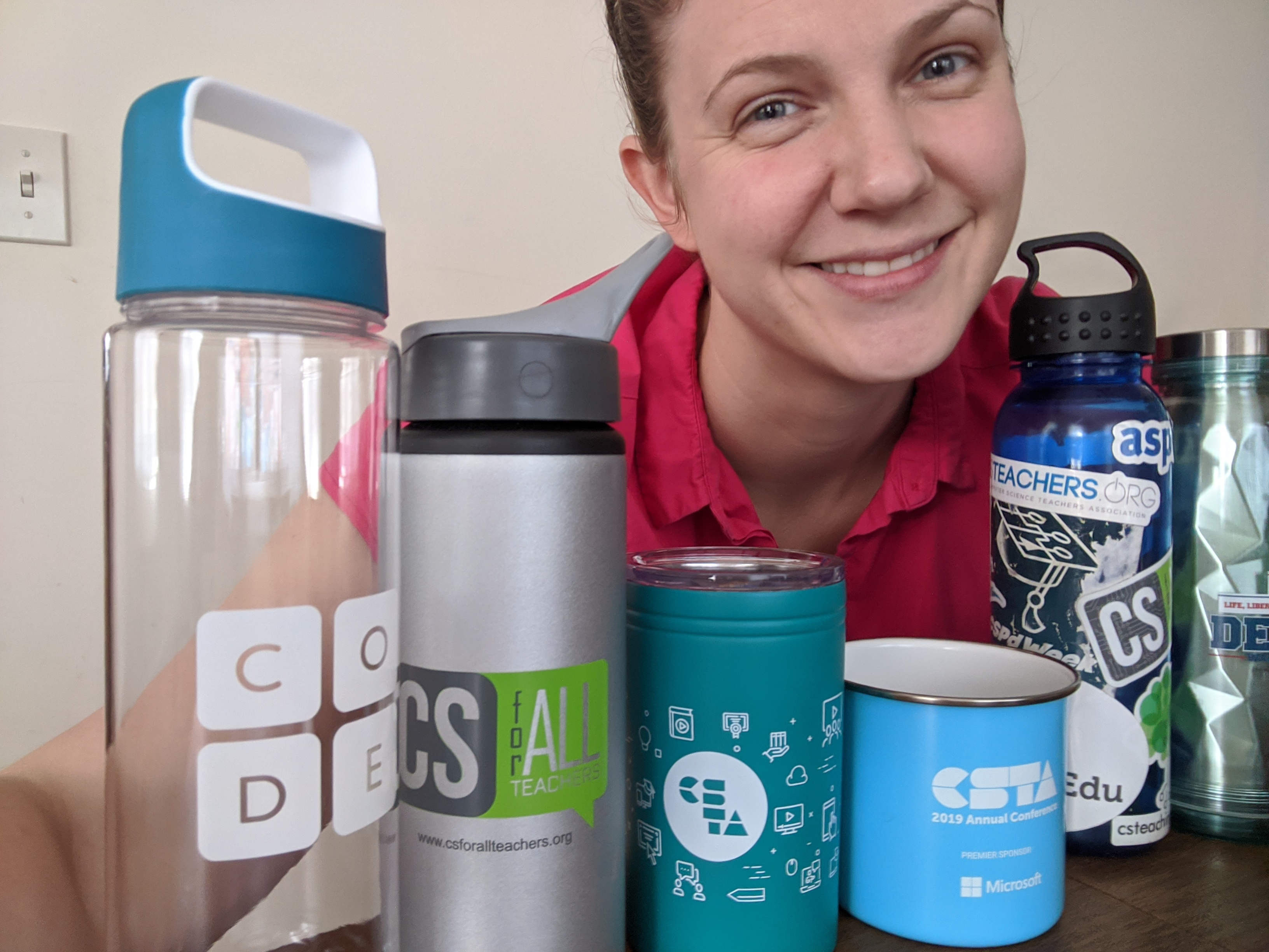 Rebekah Lang poses with water bottles with CS stickers on them.